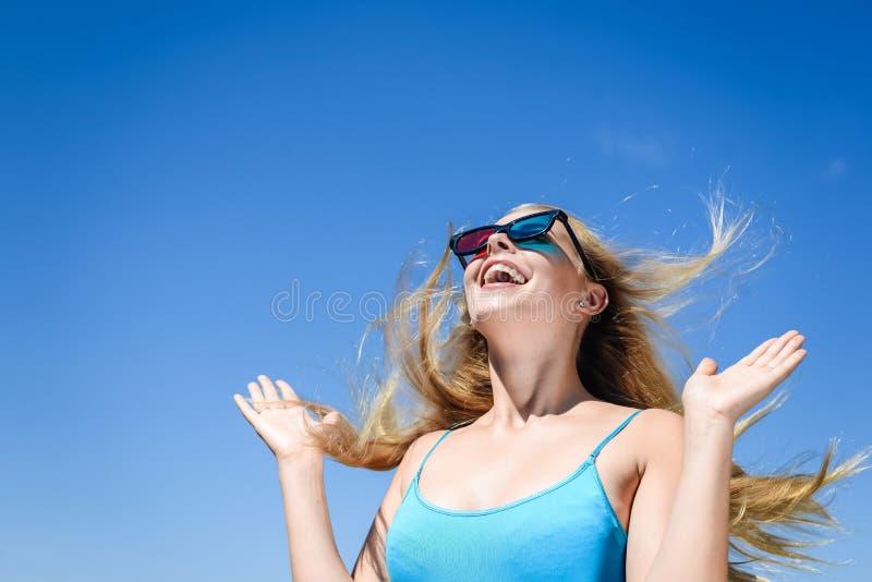 Красивая молодая дама смотря кино с стеклами 3D, голубую светлую предпосылку стоковое фото