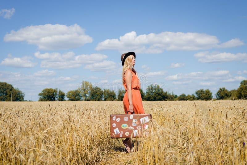 Красивая молодая дама с чемоданом на сельской местности ландшафта предпосылке outdoors стоковая фотография