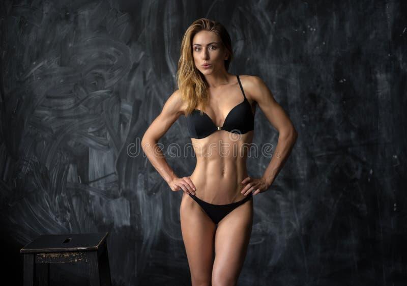 Красивая молодая атлетическая девушка в нижнем белье на темной предпосылке стоковые фотографии rf