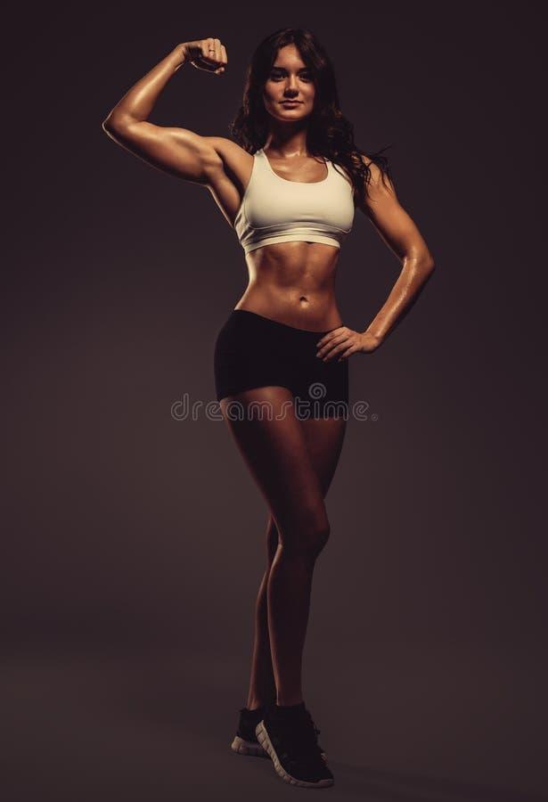 Красивая молодая атлетическая женщина показывая бицепс стоковое фото rf
