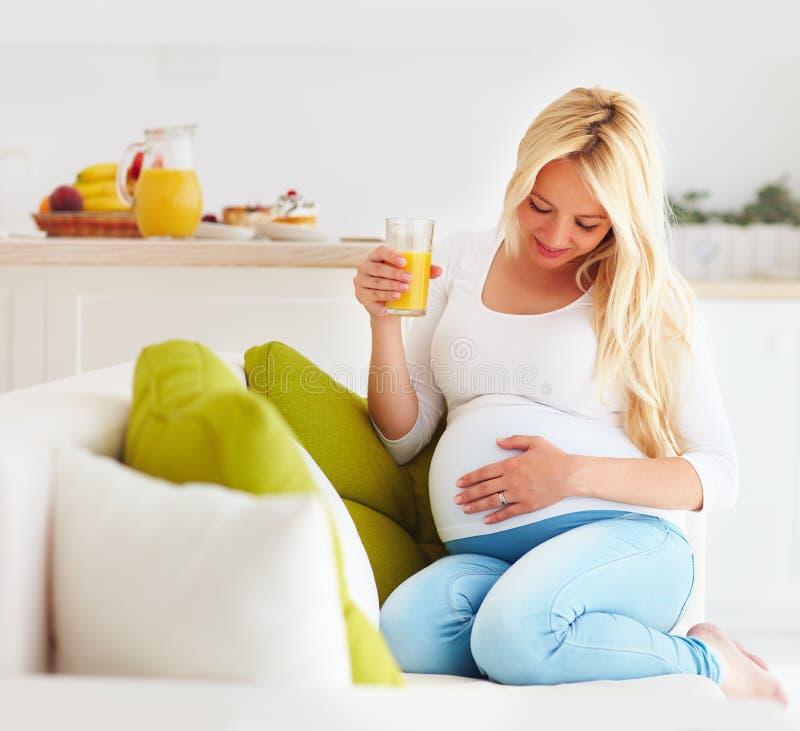 Красивая молодая беременная женщина сидя на софе дома с стеклом свежего сока стоковые фото