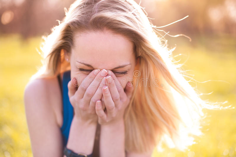 Красивая молодая белокурая девушка смеется над heartily стоковое изображение
