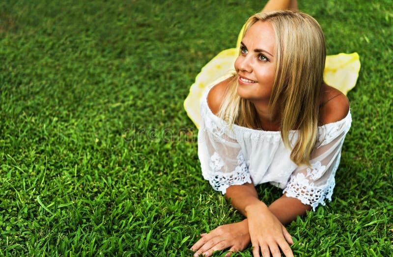 Красивая молодая белокурая женщина кладя на траву стоковое изображение