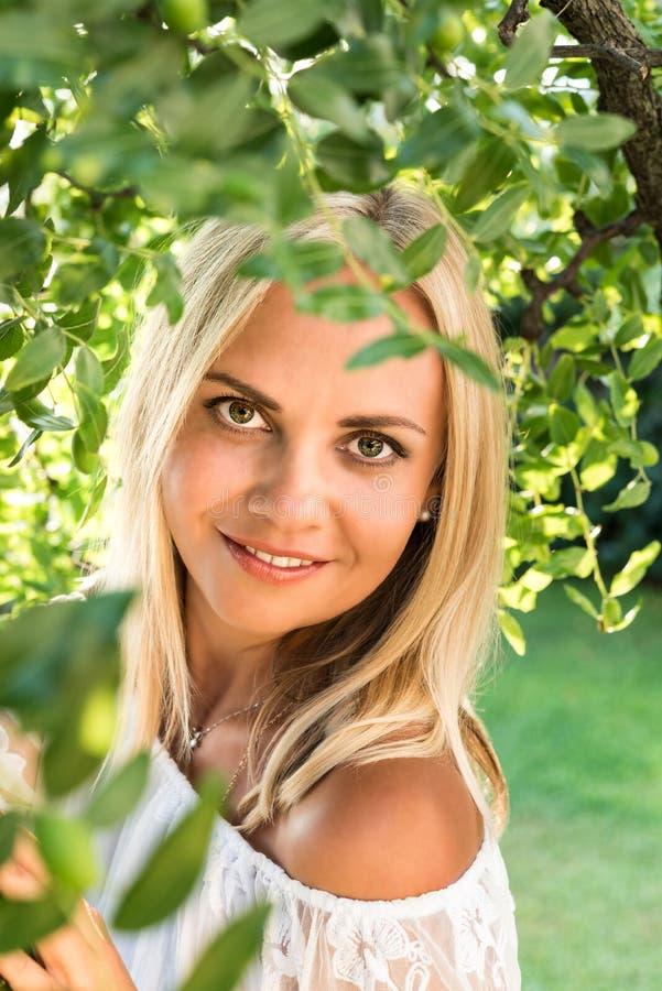 Красивая молодая белокурая женщина под деревом с стоковое изображение
