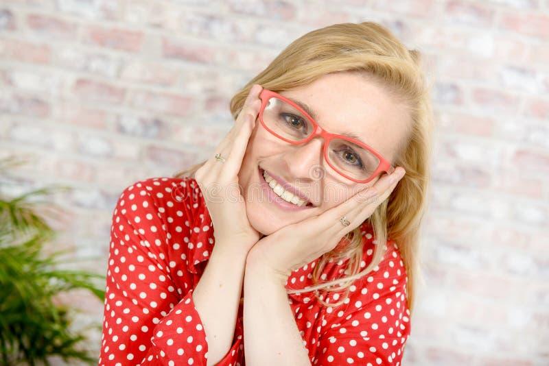 Красивая молодая белокурая женщина с красными стеклами стоковое фото