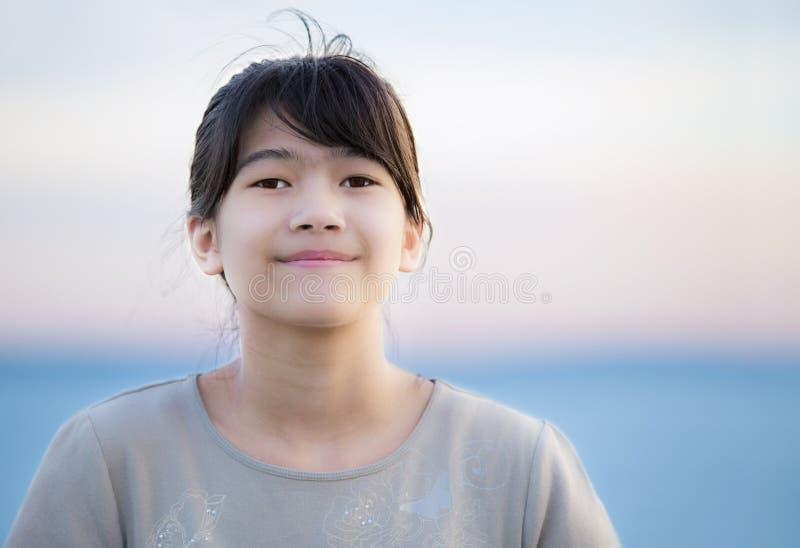 Красивая молодая девушка preteen наслаждаясь outdoors озером на заходе солнца стоковая фотография