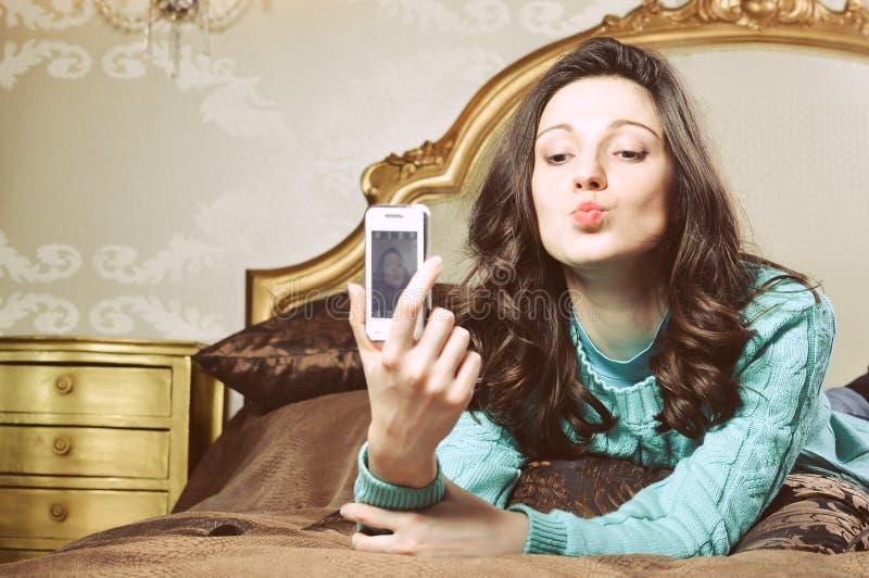 Красивая молодая женщина брюнет в кровати усмехаясь принимающ selfie стоковое изображение rf