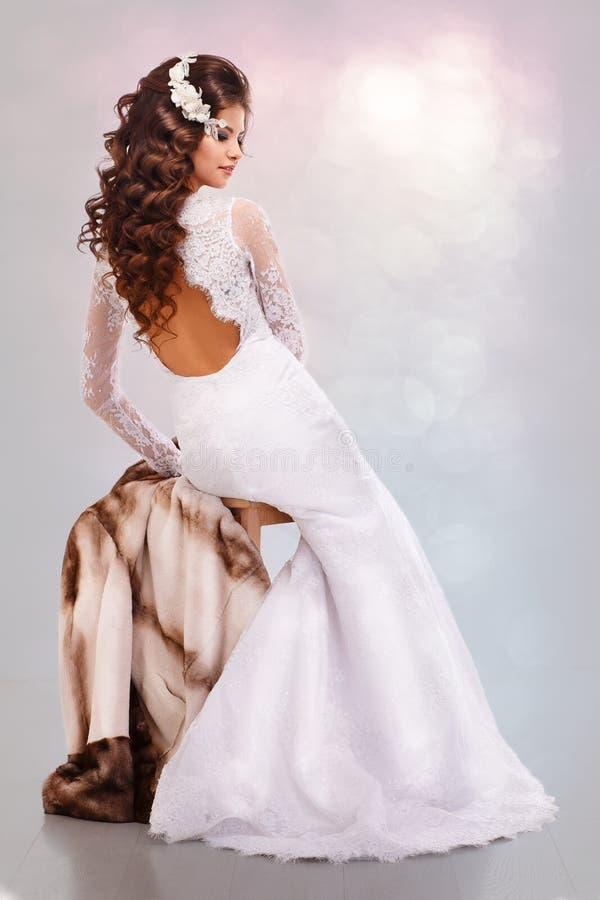Красивая молодая женщина брюнет в платье свадьбы сидит на задней части пальто норки стоковая фотография rf