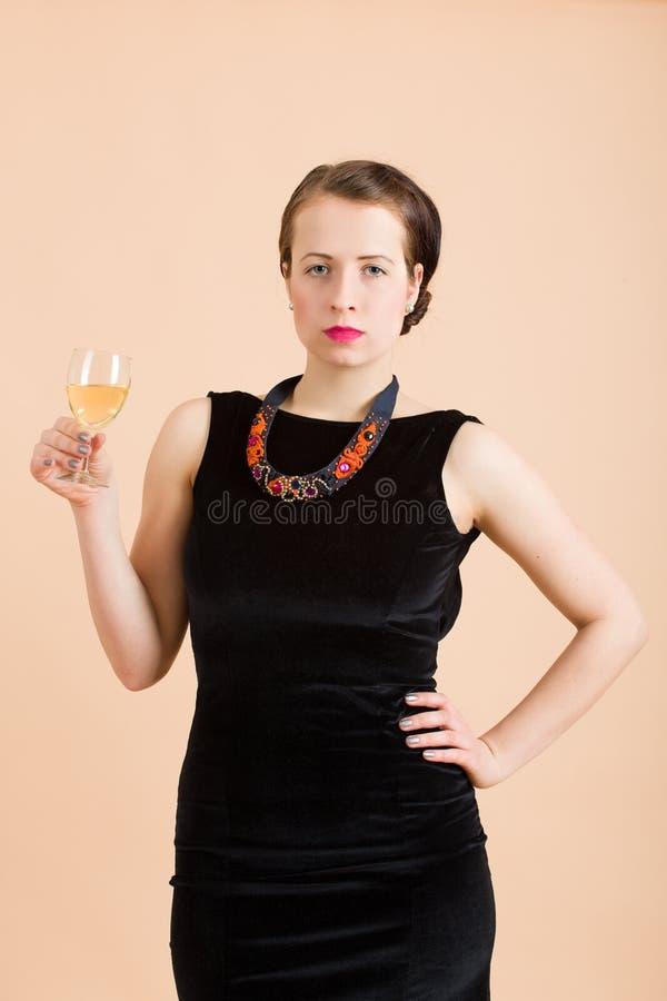 Красивая молодая женщина брюнет держа стекло белого вина стоковое изображение rf