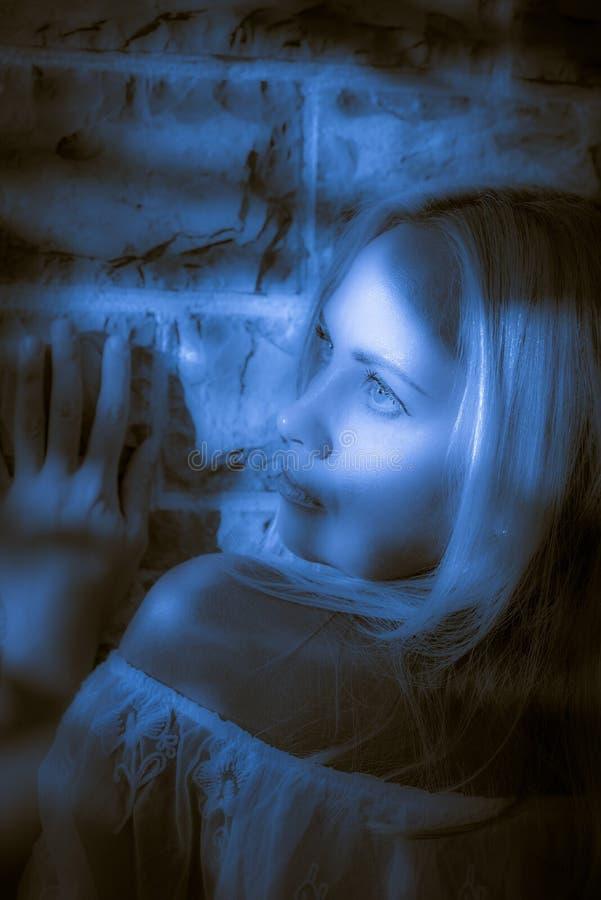 Красивая молодая женщина близко при стена наблюдая дальше стоковая фотография