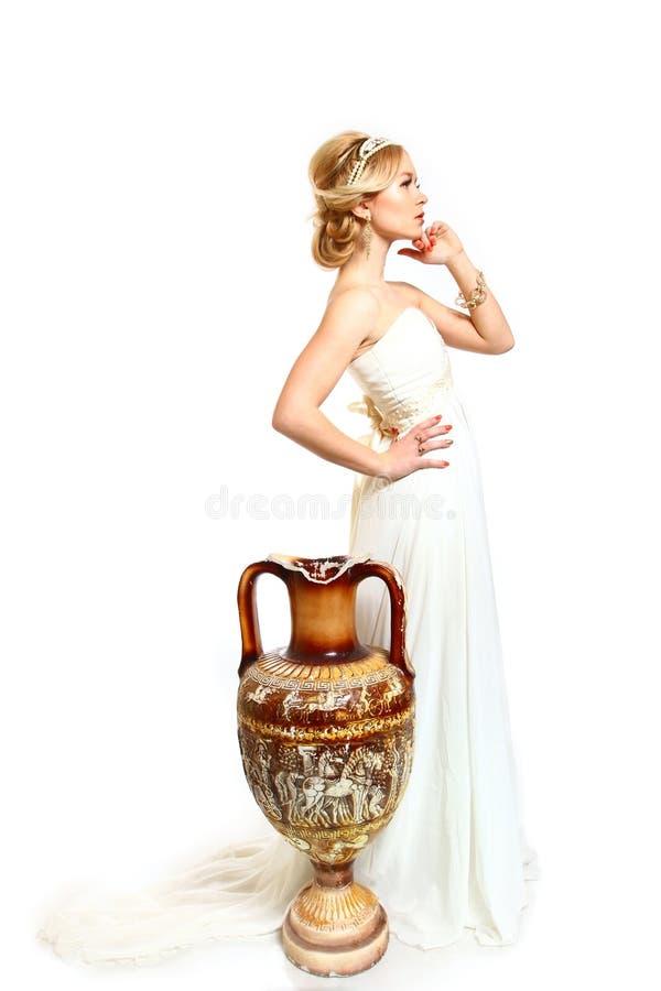 Красивая молодая женщина ввела грека в моду с амфорой на белом backgr стоковые фотографии rf