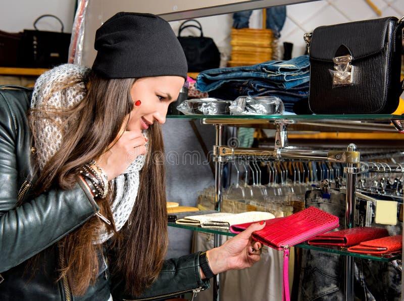 Красивая молодая женщина выбирая кожаное портмоне стоковое изображение rf