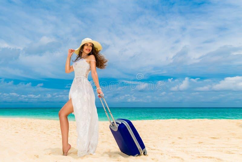 Красивая молодая женщина в белых платье и соломенной шляпе с чемоданом на тропическом пляже стоковое фото
