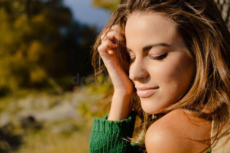 Красивая молодая женщина в зеленом свитере грея на солнце дальше стоковые изображения rf