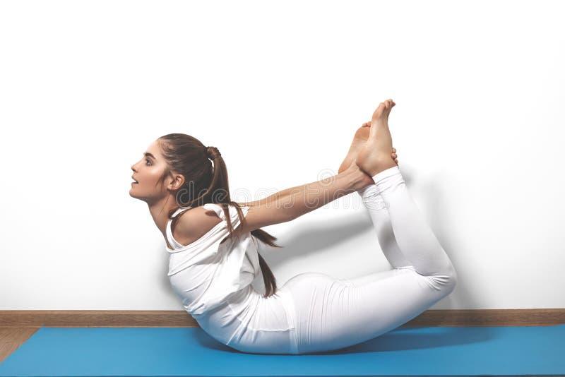 Красивая молодая женщина в йоге представляя на предпосылке студии стоковые фотографии rf