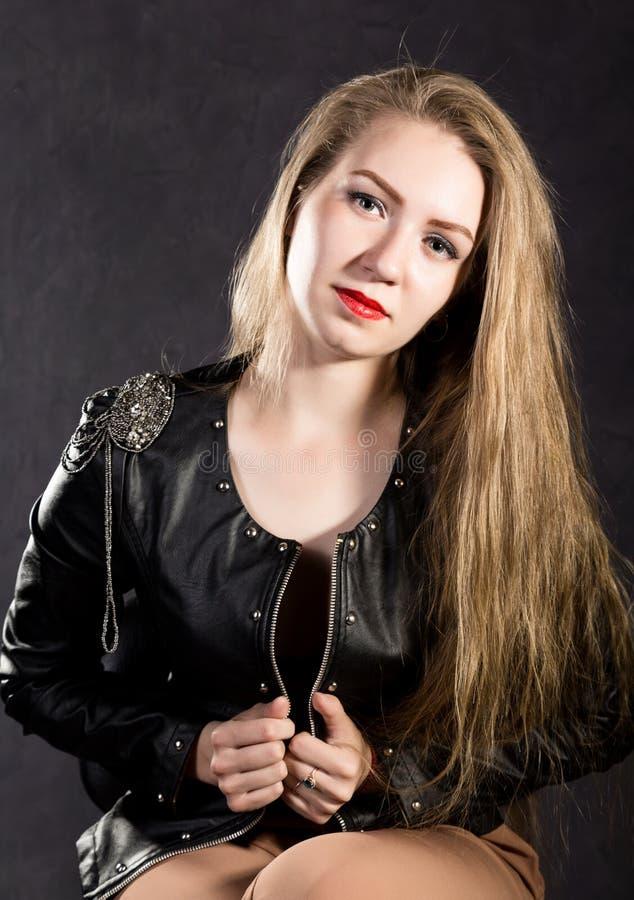 Красивая молодая женщина в кожаной куртке представляя на серой предпосылке стоковая фотография