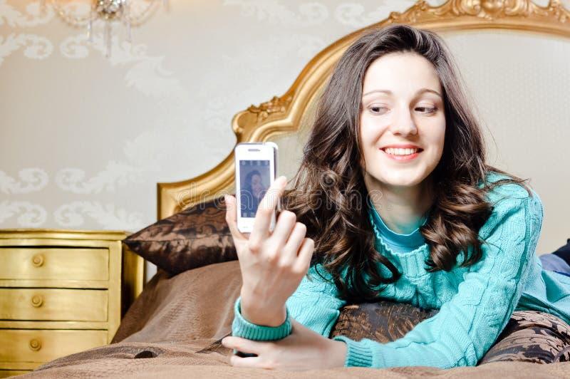 Красивая молодая женщина в кровати усмехаясь принимающ selfie стоковое изображение