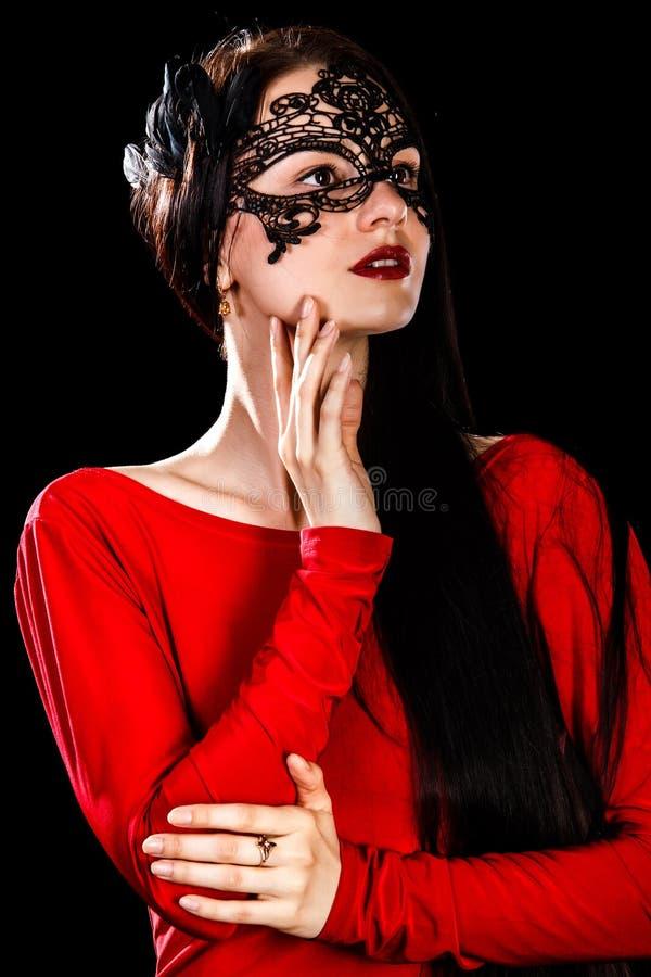 Красивая молодая женщина в черной маске и красном платье стоковые фотографии rf