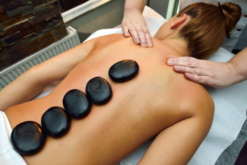 Красивая молодая женщина лежа вниз пока терапевт массажа mas стоковая фотография