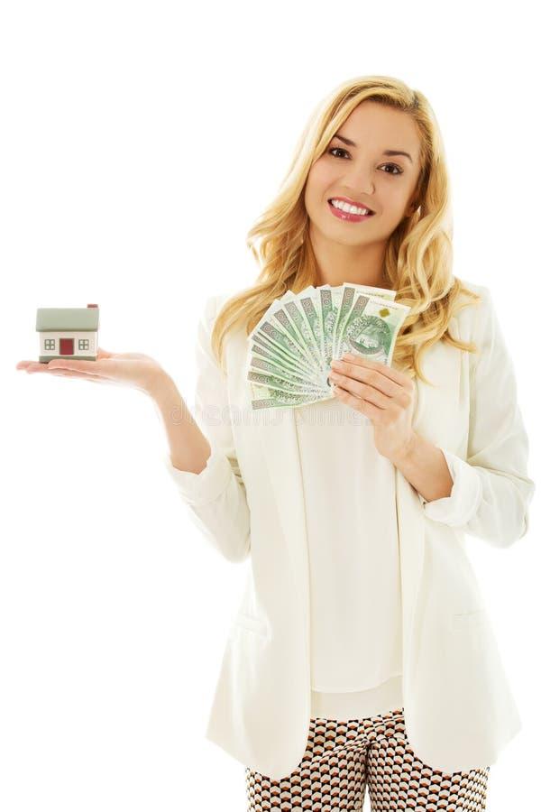 Красивая молодая женщина держа счеты и модель дома - концепцию займа недвижимости стоковые изображения