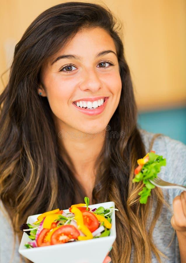 Красивая молодая женщина есть шар здорового органического салата стоковые изображения rf