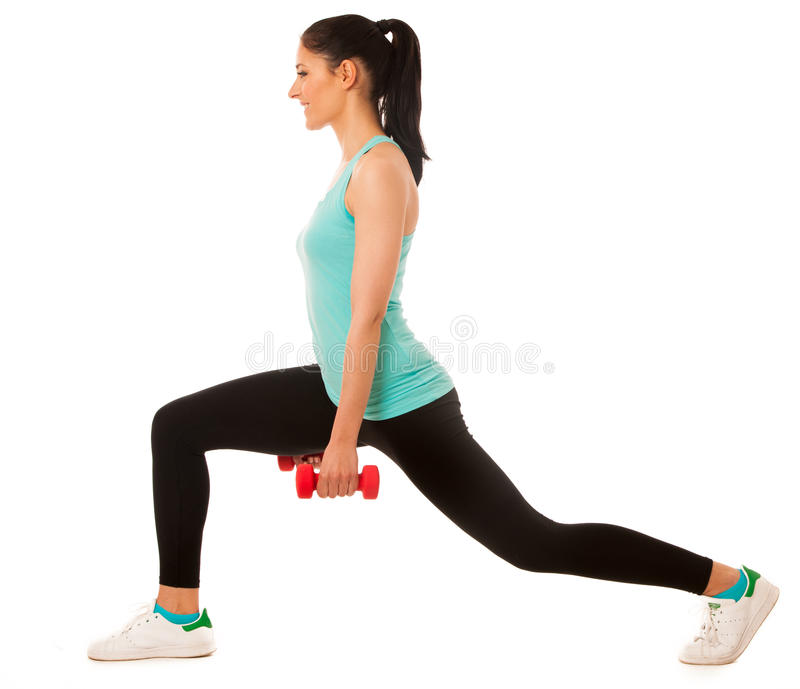 Красивая молодая женщина делая тренировку выпада с красными гантелями внутри стоковая фотография