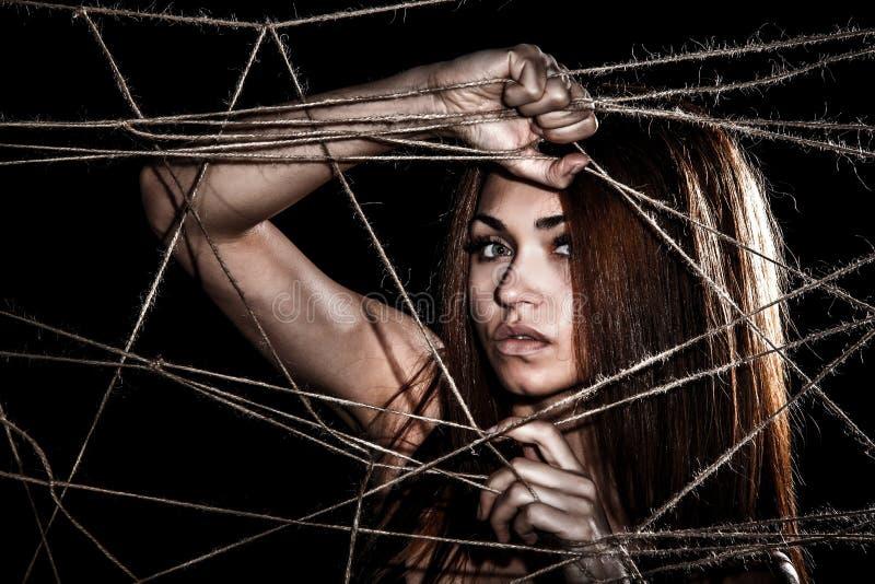 Красивая молодая женщина за переплетенными веревочками стоковые изображения