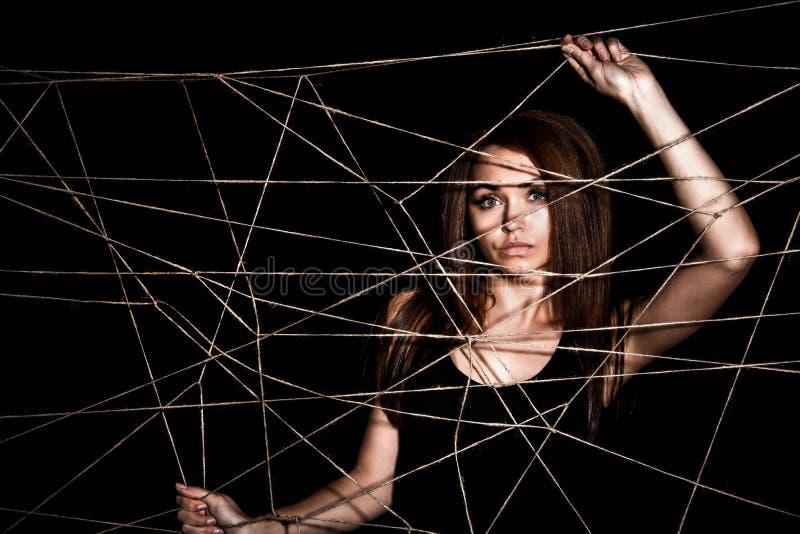 Красивая молодая женщина за сетью веревочек стоковые изображения