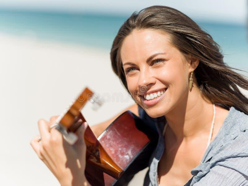 Красивая молодая женщина играя гитару на пляже стоковые изображения rf