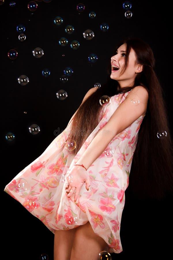 Красивая молодая женщина играя с пузырями мыла стоковое фото rf