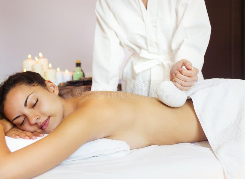 Красивая молодая женщина имея задний массаж с мешком риса стоковые фото