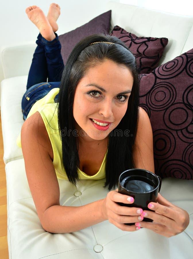 Красивая молодая женщина имея кофе сидя на софе стоковое фото