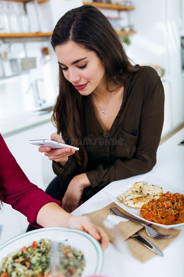 Красивая молодая женщина используя ее мобильный телефон пока ел стоковые изображения rf