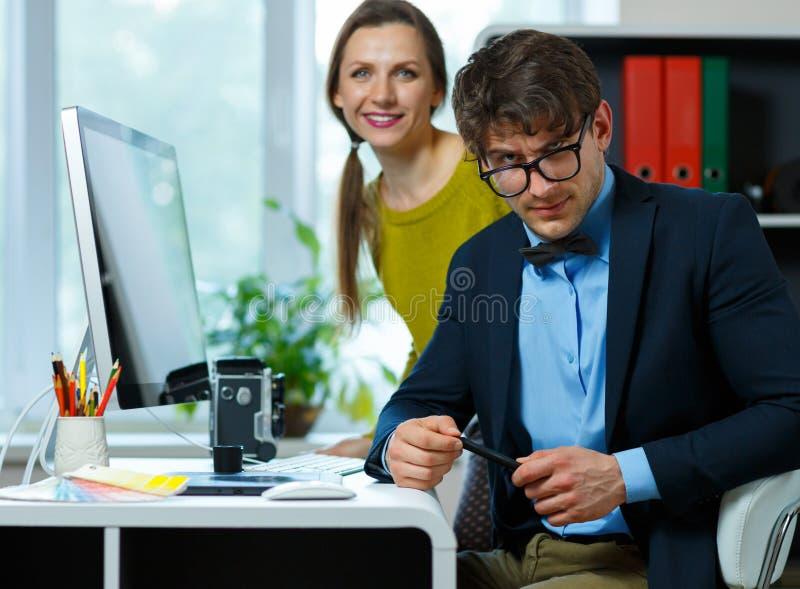 Красивая молодая женщина и человек работая от дома стоковое изображение rf
