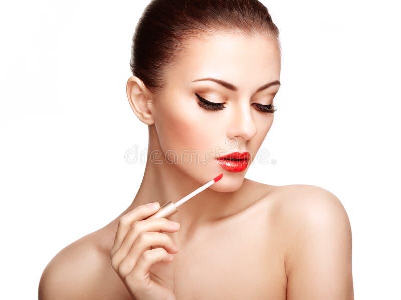 Красивая молодая женщина красит губы с губной помадой стоковое изображение rf
