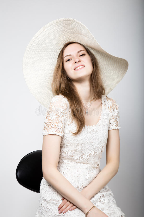 Красивая молодая женщина нося белое платье и высокие пятки, сидя на стуле стоковое изображение rf