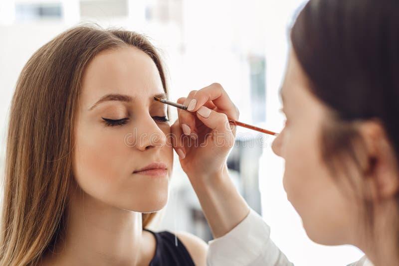 Красивая молодая женщина получает процедуру по коррекции брови стоковая фотография