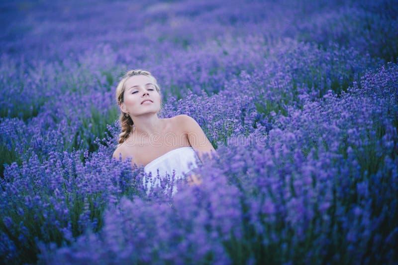 Красивая молодая женщина представляя в поле лаванды стоковые фотографии rf