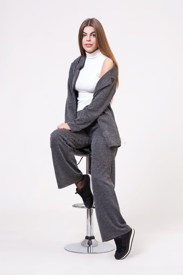 Красивая молодая женщина представляя в сером костюме на белой предпосылке стоковое фото rf