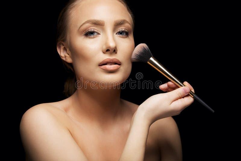 Красивая молодая женщина прикладывая учреждение стоковая фотография rf