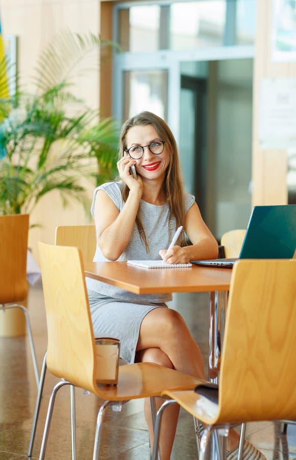 Красивая молодая женщина работая с компьтер-книжкой и говоря на c стоковые изображения