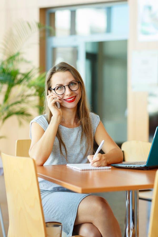 Красивая молодая женщина работая с компьтер-книжкой и говоря на c стоковое изображение