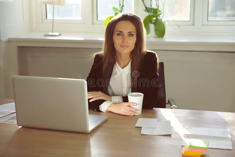 Красивая молодая женщина сидя в ее домашнем офисе стоковые фото