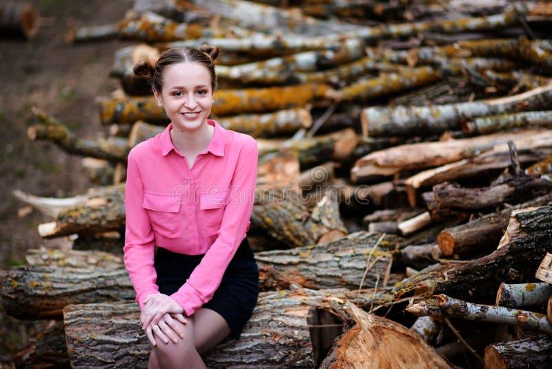 Красивая молодая женщина сидя на стоге валить стволов дерева в лесе стоковые фотографии rf
