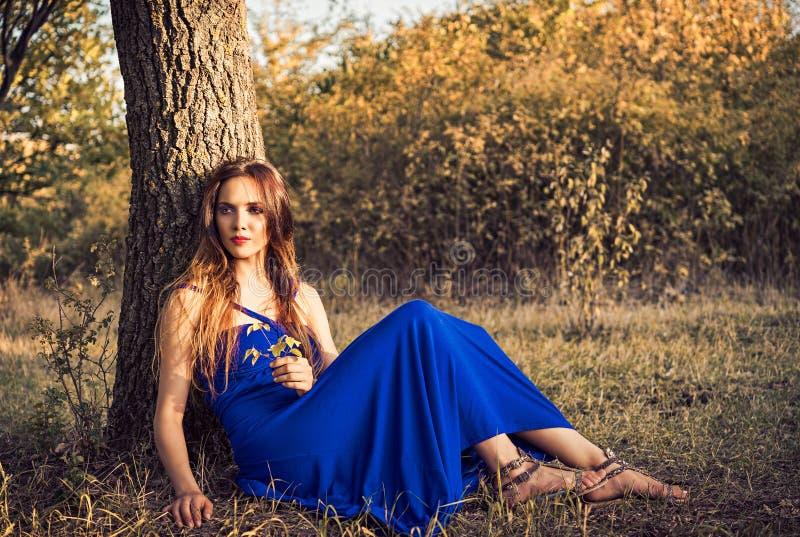 Download Красивая молодая женщина сидя под деревом время захода солнца рискованного предприятия выдержки Стоковое Фото - изображение насчитывающей gaze, сад: 40580504
