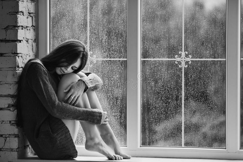 Красивая молодая женщина сидя самостоятельно близко к окну с дождем падает Сексуальная и унылая девушка Принципиальная схема один стоковое фото rf