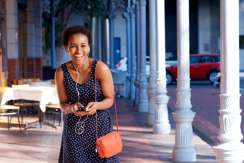 Красивая молодая женщина смеясь над с мобильным телефоном и наушниками стоковая фотография rf