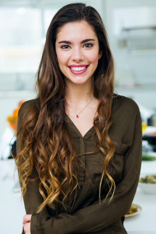 Красивая молодая женщина смотря камеру в кухне стоковые изображения rf