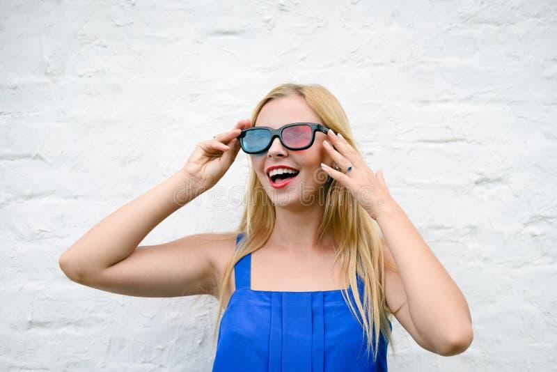 Красивая молодая женщина смотря кино при стекла 3D, возбуждая держащ руки стоковое фото