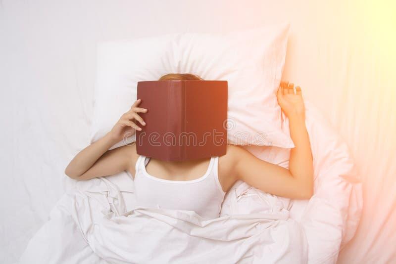 Красивая молодая женщина спать на кровати после прочитала книгу с стоковые фотографии rf